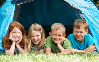 Kinder liegen im Zelt