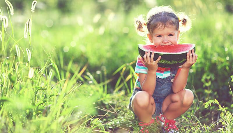 Kleines Mädchen isst Melone