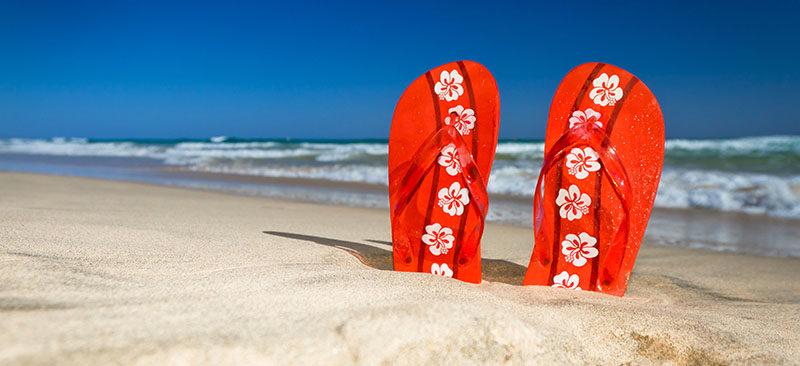 Rote Flipflops am Sandstrand